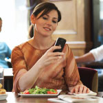 Woman sitting at a lunch table with a salad in front of her, looking at her phone.