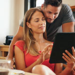 Wife sitting on a couch with her husband resting his head on her shoulder so they can both look at the tablet she is holding up