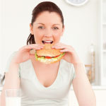 Woman with dark hair and a white shirt holding up a burger she is about to take a bite out of