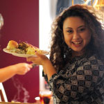 Woman with dark curly hair holding a plate of food and smiling