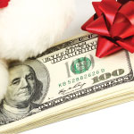 Stack of money with a Santa hat and a red bow
