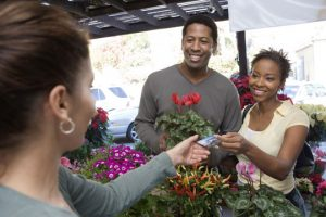 Couple purchasing flowers at a market with a debit card