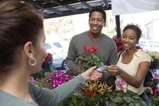 Nice couple purchasing flowers at a market with their OKFCU debit card