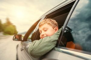 Kid hangs his head out the window enjoying the breeze during a car ride